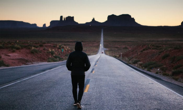 Photo of a person facing a long road ahead.